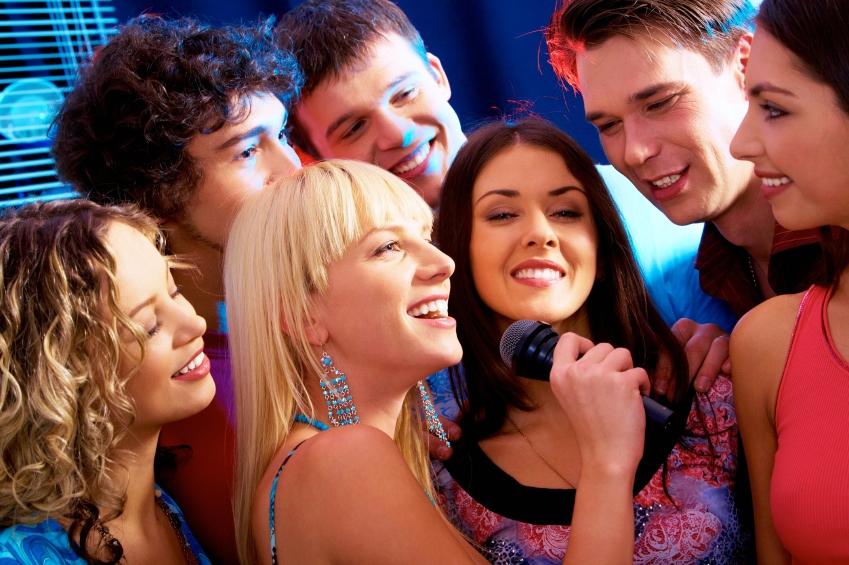 happy colleagues singing karaoke